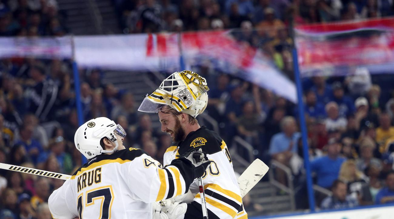 Boston Bruins goalie Jonas Gustavsson (50), of Sweden, speaks with defenseman Torey Krug (47) after blocking a shot on goal during the second period of an NHL hockey game against the Tampa Bay Lightning, Tuesday, March 8, 2016, in Tampa, Fla. (AP Photo/Br