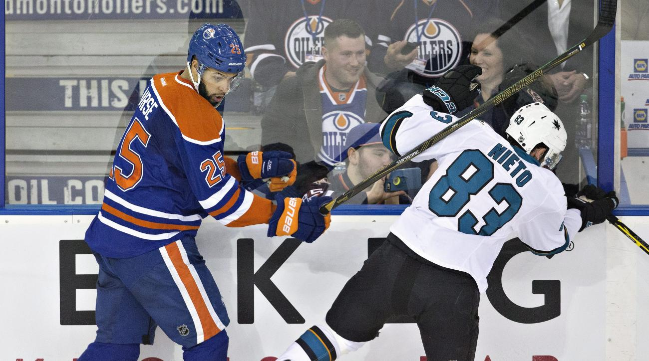 San Jose Sharks ' Matt Nieto (83) is checked by Edmonton Oilers' Darnell Nurse (25) during second period NHL action in Edmonton, Alberta, Tuesday March 8, 2016. (Jason Franson/The Canadian Press via AP)