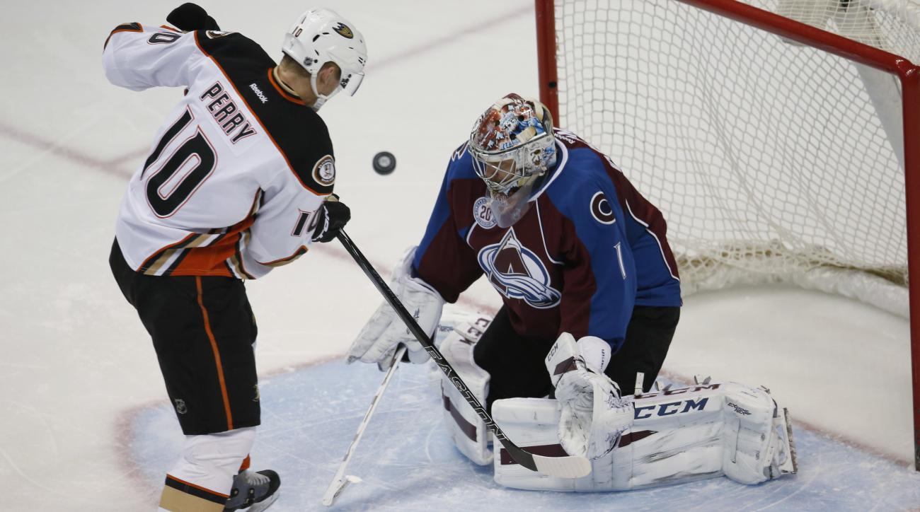 Anaheim Ducks right wing Corey Perry, left, directs a shot at Colorado Avalanche goalie Semyon Varlamov, of Russia, in the first period of an NHL hockey game Wednesday, March 9, 2016, in Denver. (AP Photo/David Zalubowski)