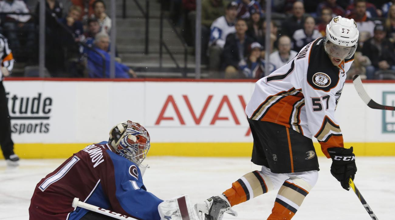 Anaheim Ducks left wing David Perron, right, watches as his redirected shot slips between the legs of Colorado Avalanche goalie Semyon Varlamov, of Russia, before sliding past the net in the second period of an NHL hockey game Wednesday, March 9, 2016, in