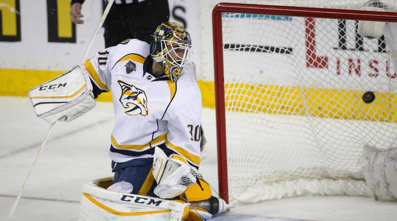 Nashville Predators goalie Carter Hutton looks back as a goal by Calgary Flames' Mikael Backlund enters the net during overtime of an NHL hockey game in Calgary, Alberta, Wednesday, March 9, 2016. (Jeff McIntosh/The Canadian Press via AP)