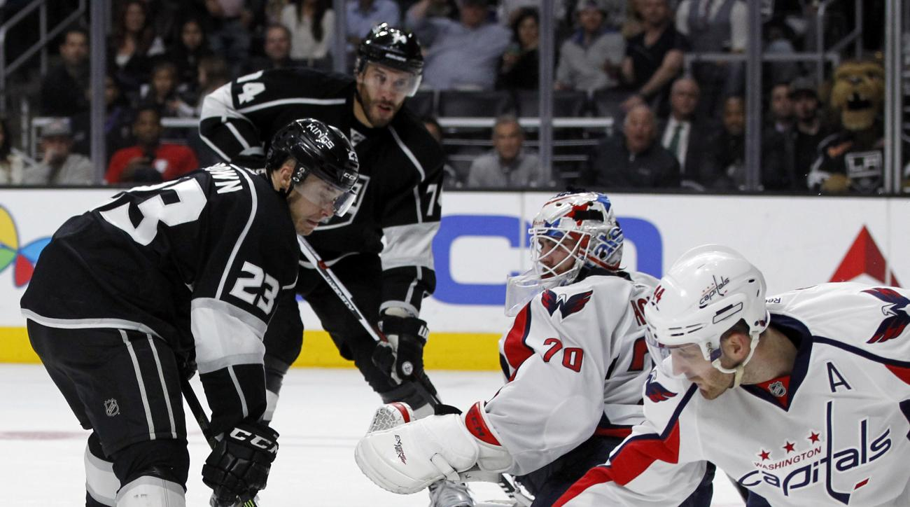 Washington Capitals goalie Braden Holtby, second from right, makes a save with defenseman Brooks Orpik, right, on a shot by Los Angeles Kings right wing Dustin Brown (23), with left wing Dwight King (74) looking on, during the second period of an NHL hock