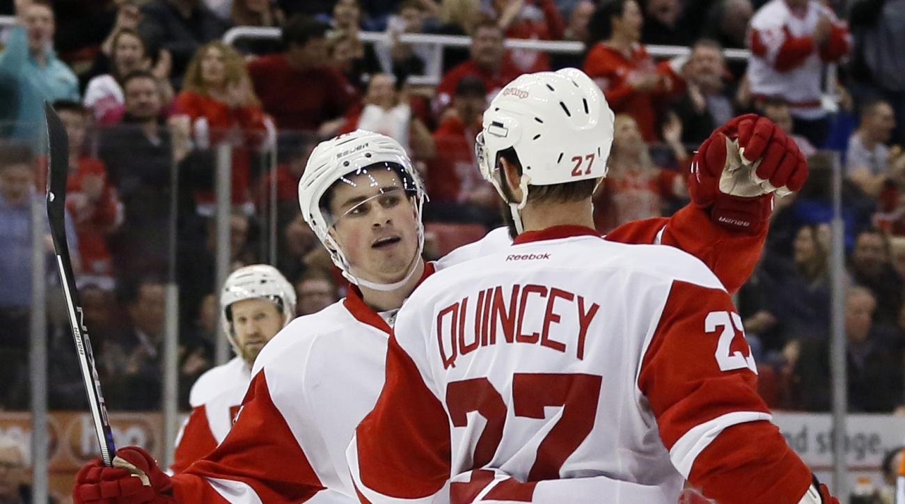 Detroit Red Wings' Dylan Larkin (71) celebrates his second-period goal against the Winnipeg Jets with teammate Kyle Quincey (27) during an NHL hockey game Thursday, March 10, 2016, in Detroit. (AP Photo/Duane Burleson)