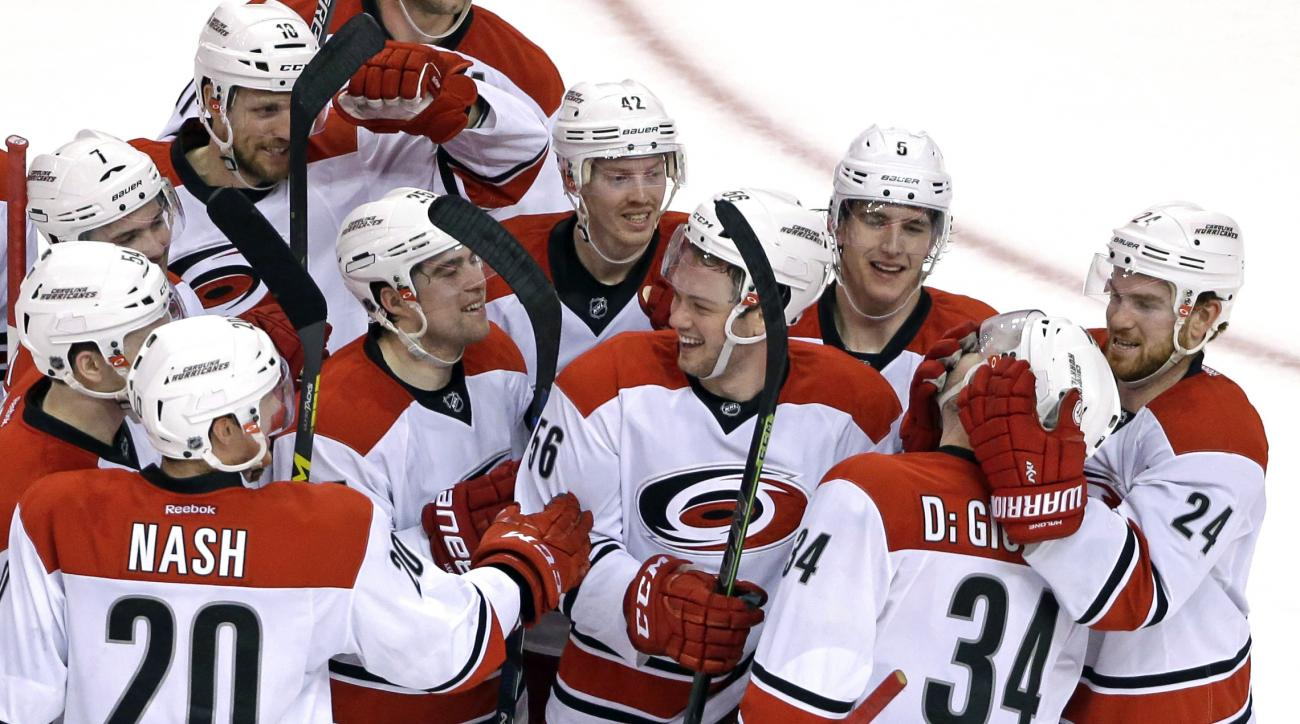 Carolina Hurricanes left wing Phil Di Giuseppe (34) is mobbed by his teammates to celebrate his winning goal against the Boston Bruins in the overtime period of an NHL hockey game, Thursday, March 10, 2016, in Boston. The Hurricanes won 3-2. (AP Photo/Eli