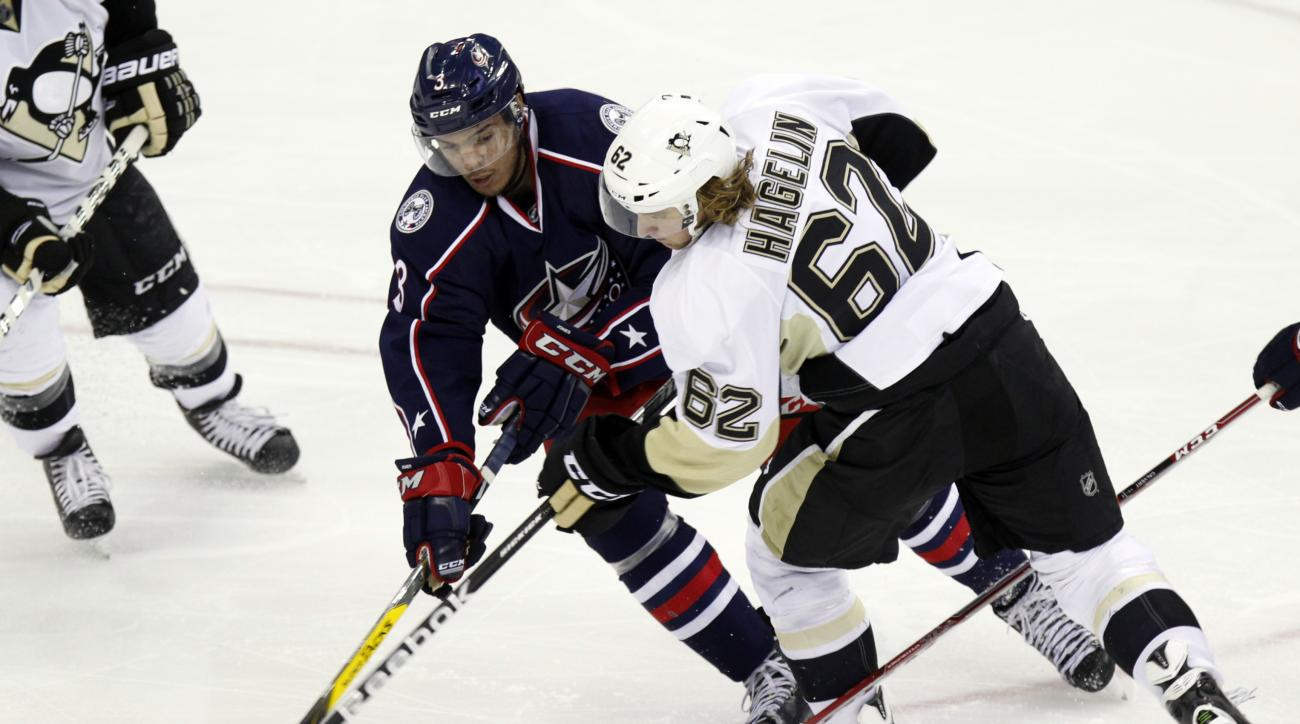 Pittsburgh Penguins' Carl Hagelin, right, of Sweden, works against Columbus Blue Jackets' Seth Jones during the third period of an NHL hockey game in Columbus, Ohio Friday, March 11, 2016. Pittsburgh won 3-2. (AP Photo/Paul Vernon)