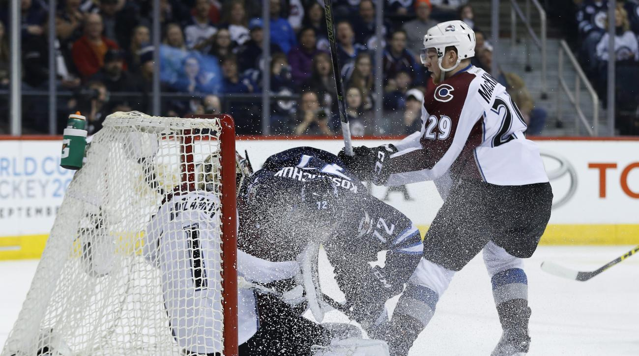 CORRECTS JETS PLAYER TO SCOTT KOSMACHUK, INSTEAD OF DREW STAFFORD - Winnipeg Jets' Scott Kosmachuk (72) crashes into Colorado Avalanche goalie Semyon Varlamov (1) as Nathan MacKinnon (29) defends during the second period of an NHL hockey game Saturday, Ma