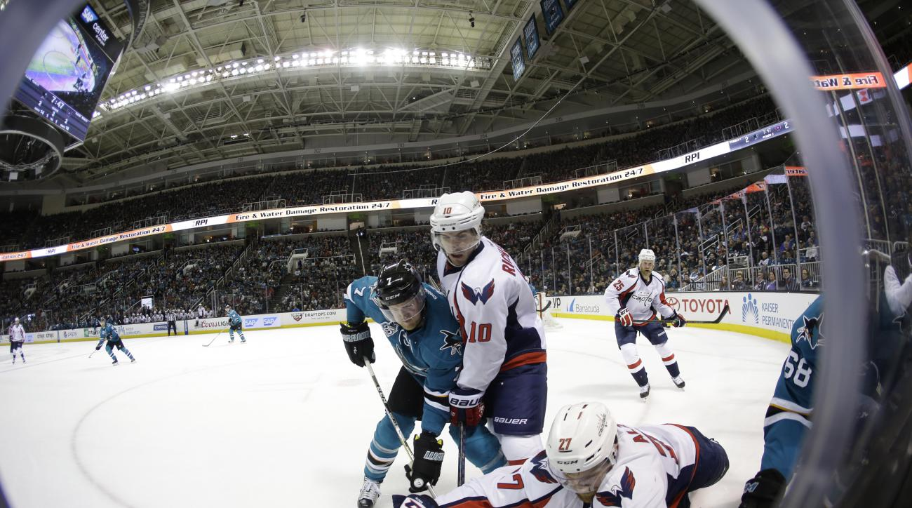 San Jose Sharks' Paul Martin (7) battles for the puck against Washington Capitals' Mike Richards (10) and Karl Alzner (27) during the second period of an NHL hockey game Saturday, March 12, 2016, in San Jose, Calif. (AP Photo/Marcio Jose Sanchez)