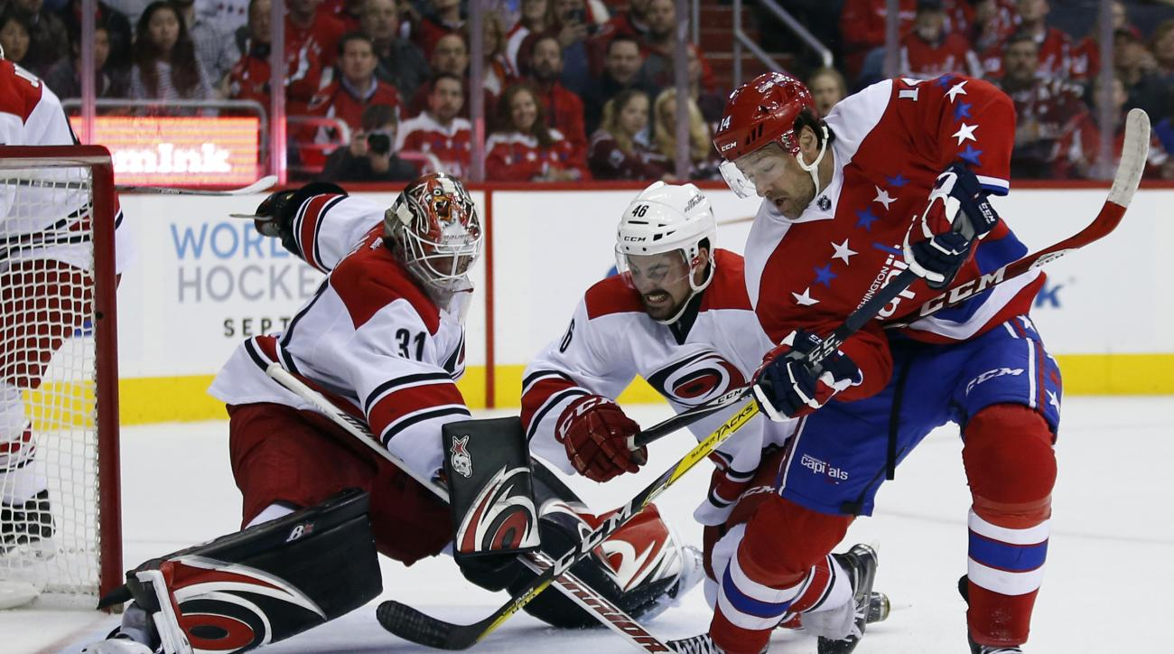 Carolina Hurricanes goalie Eddie Lack (31), from Sweden, reaches for the puck as defenseman Trevor Carrick (46) defends against Washington Capitals right wing Justin Williams (14) in the first period of an NHL hockey game, Tuesday, March 15, 2016, in Wash