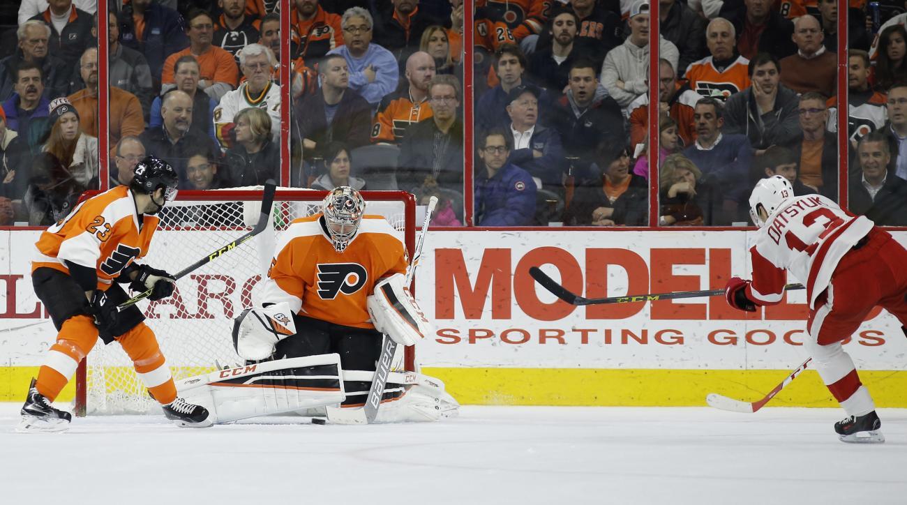 Detroit Red Wings' Pavel Datsyuk, right, scores a goal under Philadelphia Flyers' Steve Mason, center, as Brandon Manning looks on during the second period of an NHL hockey game, Tuesday, March 15, 2016, in Philadelphia. (AP Photo/Matt Slocum)