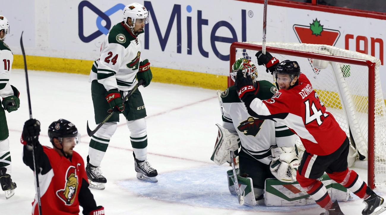 Minnesota Wild goaltender Devan Dubnyk (40) and teammate Matt Dumba (24) react as Ottawa Senators' Erik Karlsson, front left, celebrates his overtime goal with teammate Ryan Dzingel (43) in an NHL hockey game Tuesday, March 15, 2016, in Ottawa, Ontario. (