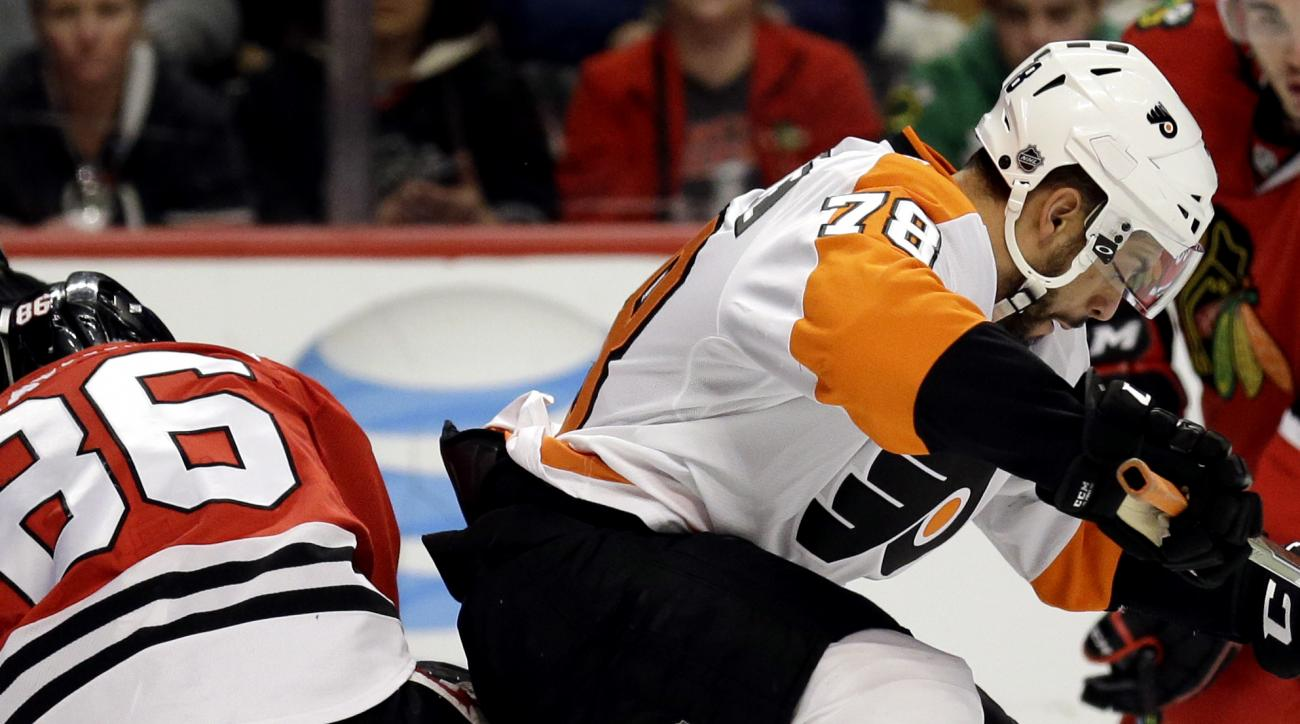 Philadelphia Flyers left wing Pierre-Edouard Bellemare, right, battles for the puck against Chicago Blackhawks center Teuvo Teravainen during the first period of an NHL hockey game Wednesday, March 16, 2016, in Chicago. (AP Photo/Nam Y. Huh)