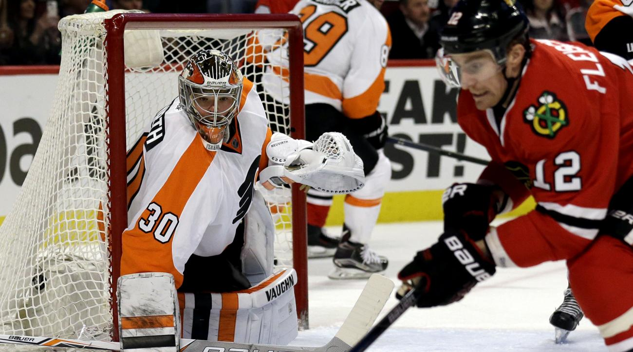 Philadelphia Flyers goalie Michal Neuvirth (30) watches as Chicago Blackhawks left wing Tomas Fleischmann (12) controls the puck during the second period of an NHL hockey game Wednesday, March 16, 2016, in Chicago. (AP Photo/Nam Y. Huh)