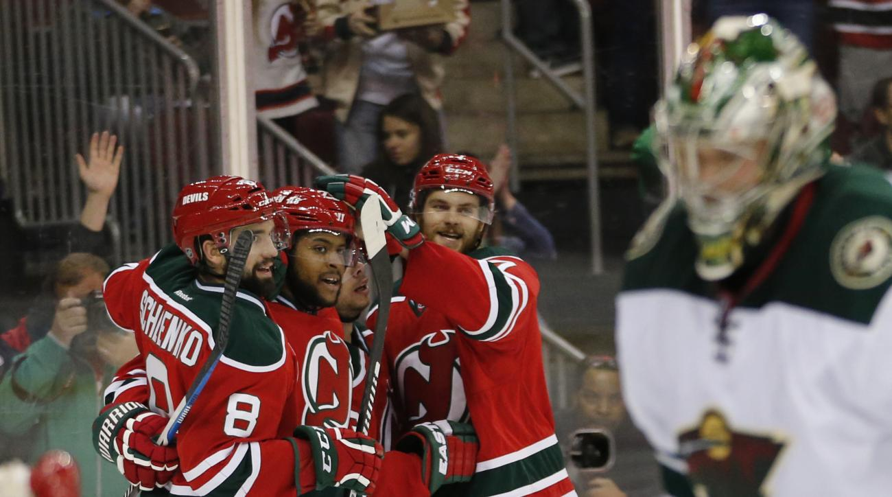 New Jersey Devils players celebrate a goal by Devante Smith-Pelly, second from left, against Minnesota Wild goalie Darcy Kuemper, right, during the second period of an NHL hockey game, Thursday, March 17, 2016, in Newark, N.J. (AP Photo/Julio Cortez)