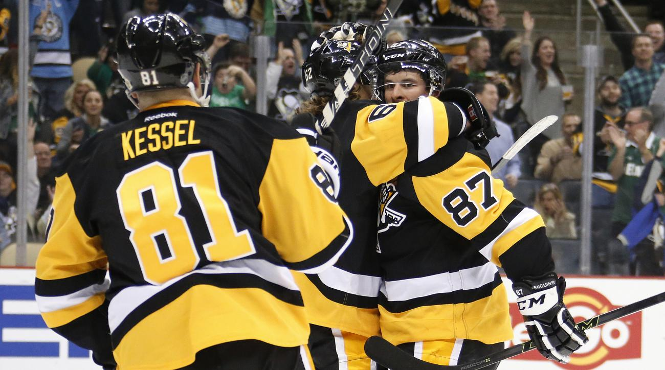 Pittsburgh Penguins' Sidney Crosby (87) celebrates his second goal of an NHL hockey game with teammates in the second period against the Carolina Hurricanes in Pittsburgh, Thursday, March 17, 2016. (AP Photo/Gene J. Puskar)
