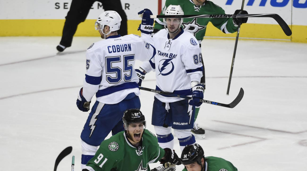 Dallas Stars left wing Jamie Benn (14) celebrates his game-winning goal with teammates Alex Goligoski (33) and  Tyler Seguin (91), in front of Tampa Bay Lightning defenseman Braydon Coburn (55) and Nikita Kucherov (86) during the third period of their NHL