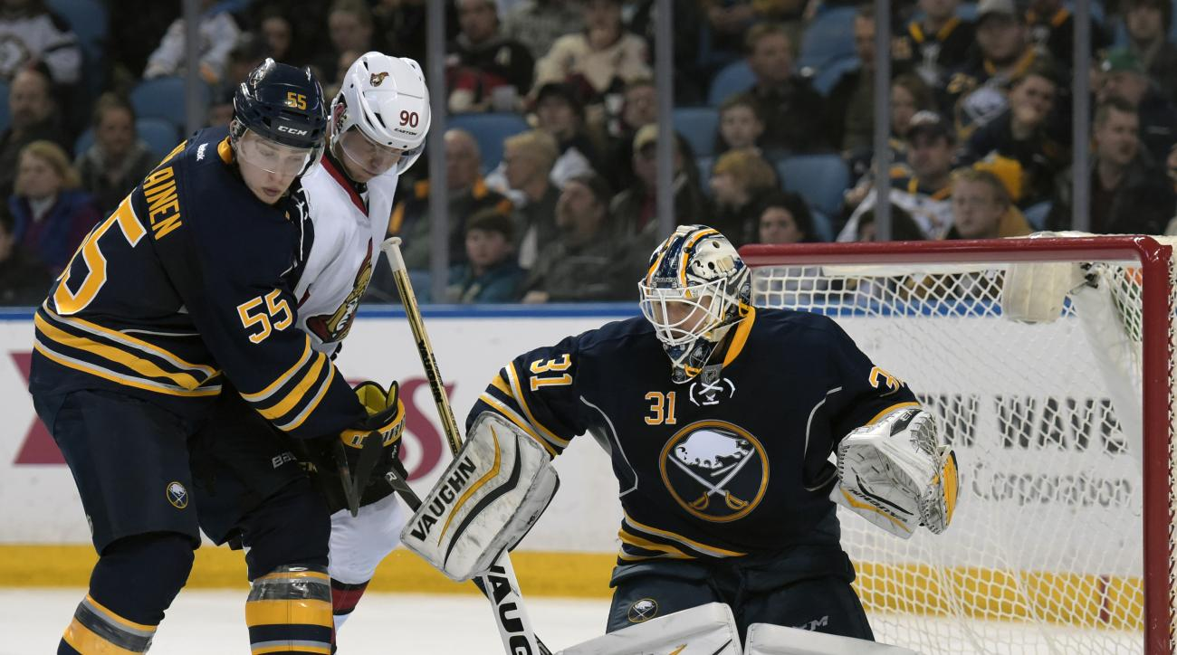 Buffalo Sabres defenseman Rasmus Ristolainen (55) tangles with Ottawa Senators right winger Alex Chiasson (90) as Sabres goaltender Chad Johnson (31) makes a save during the second period of an NHL hockey game, Friday, March 18, 2016, in Buffalo, N.Y. (AP