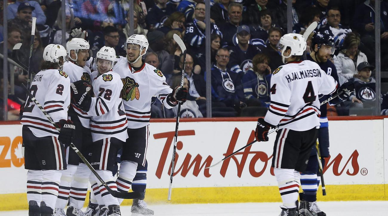 Chicago Blackhawks' Duncan Keith (2), Marian Hossa (81), Artemi Panarin (72) and Artem Anisimov (15) celebrate Hossa's goal against the Winnipeg Jets during second-period NHL hockey game action in Winnipeg, Manitoba, Friday, March 18, 2016. (John Woods/Th