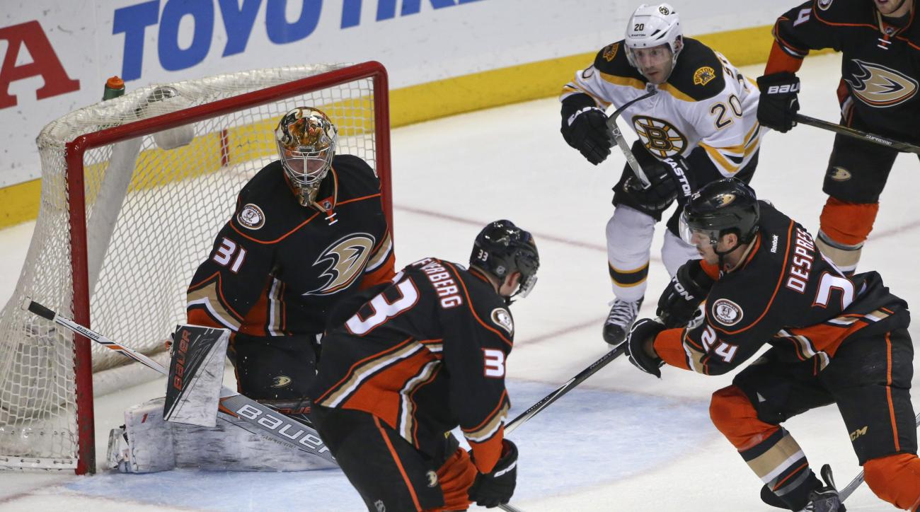 Anaheim Ducks defenseman Simon Despres, right, clears the puck from the front of the net as goalie Frederik Andersen and left wing Jakob Silfverberg watch during the first period of an NHL hockey game against the Boston Bruins on Friday, March 18, 2016, i