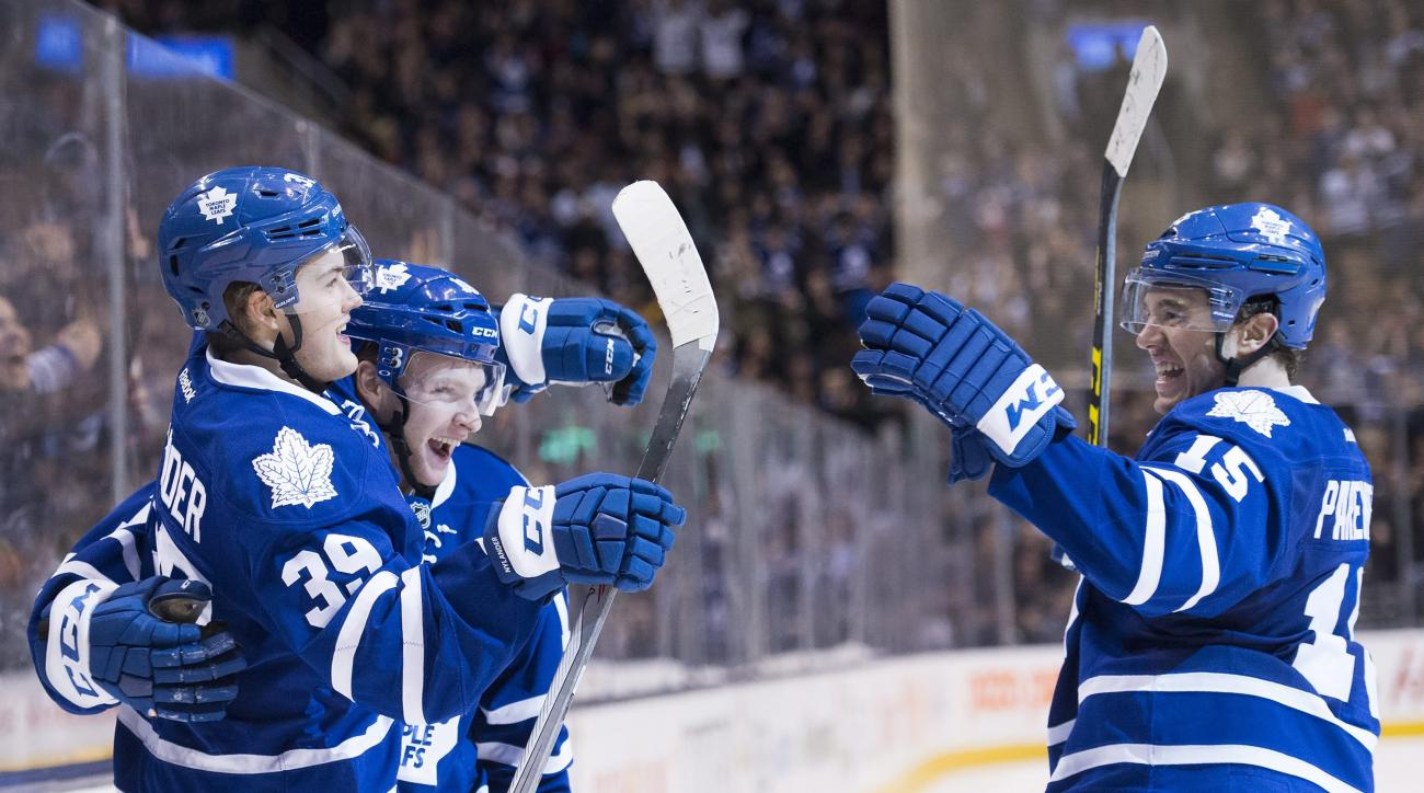 Toronto Maple Leafs' right wing William Nylander (39) celebrates his goal with teammates Connor Brown (16) and P.A. Parenteau (15) during second period NHL hockey action in Toronto on Saturday, March 19, 2016.  (Nathan Denette/The Canadian Press via AP)