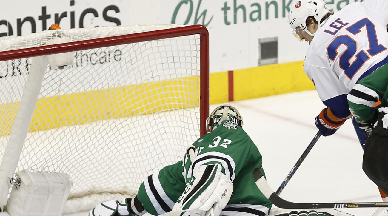 New York Islanders forward Anders Lee (27) nudges the puck wide of the net as Dallas Stars goalie Kari Lehtonen (32) defends during the second period of an NHL Hockey game, Saturday, March 19, 2016, in Dallas. (AP Photo/Brandon Wade)