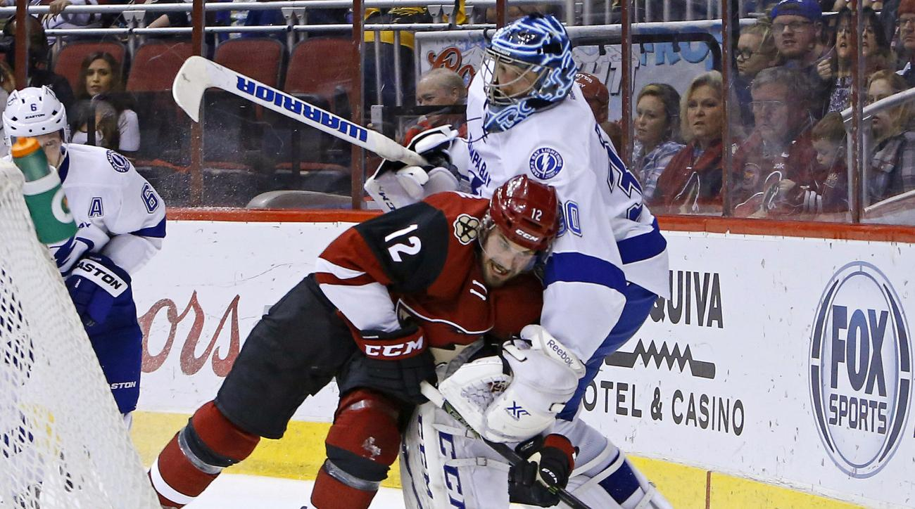 Arizona Coyotes center Brad Richardson (12) collides with Tampa Bay Lightning goalie Ben Bishop (30) as they fight for the puck during the second period of an NHL game Saturday, March 19, 2016, in Glendale, Ariz. (David Kadlubowski/The Arizona Republic vi
