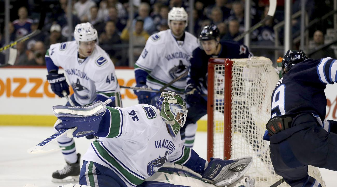 Vancouver Canucks' goalie Jacob Markstrom (25) stops Winnipeg Jets' Nic Petan (19) during the second period of an NHL hockey game Tuesday, March 22, 2016, in Winnipeg, Manitoba. (Trevor Hagan/The Canadian Press via AP)