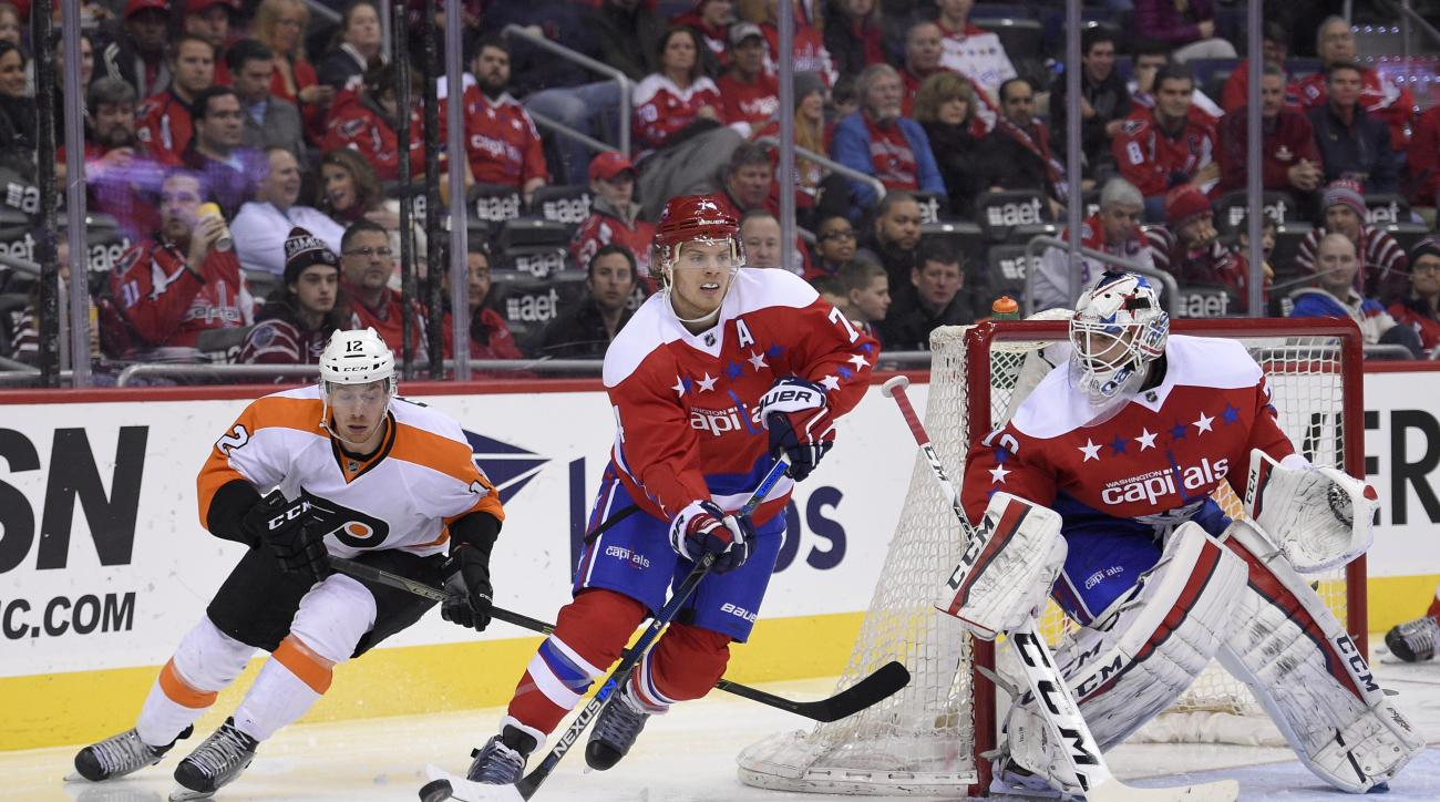 In this photo taken Feb. 7, 2016, Washington Capitals defenseman John Carlson (74) skates with the puck past Philadelphia Flyers left wing Michael Raffl (12), of Austria, during the second period of an NHL hockey game in Washington. Capitals goalie Braden