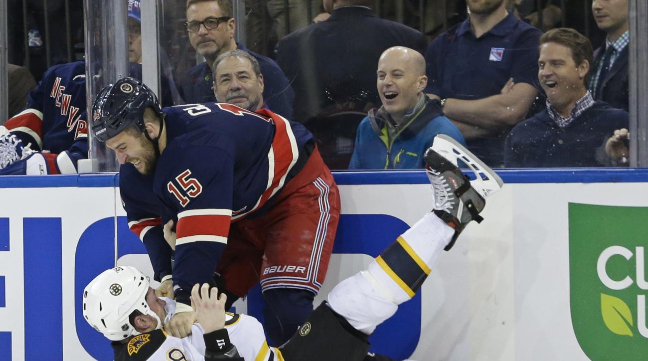 Fans react as New York Rangers' Tanner Glass (15) punches Boston Bruins' Matt Beleskey (39) during the first period of an NHL hockey game Wednesday, March 23, 2016, in New York. (AP Photo/Frank Franklin II)