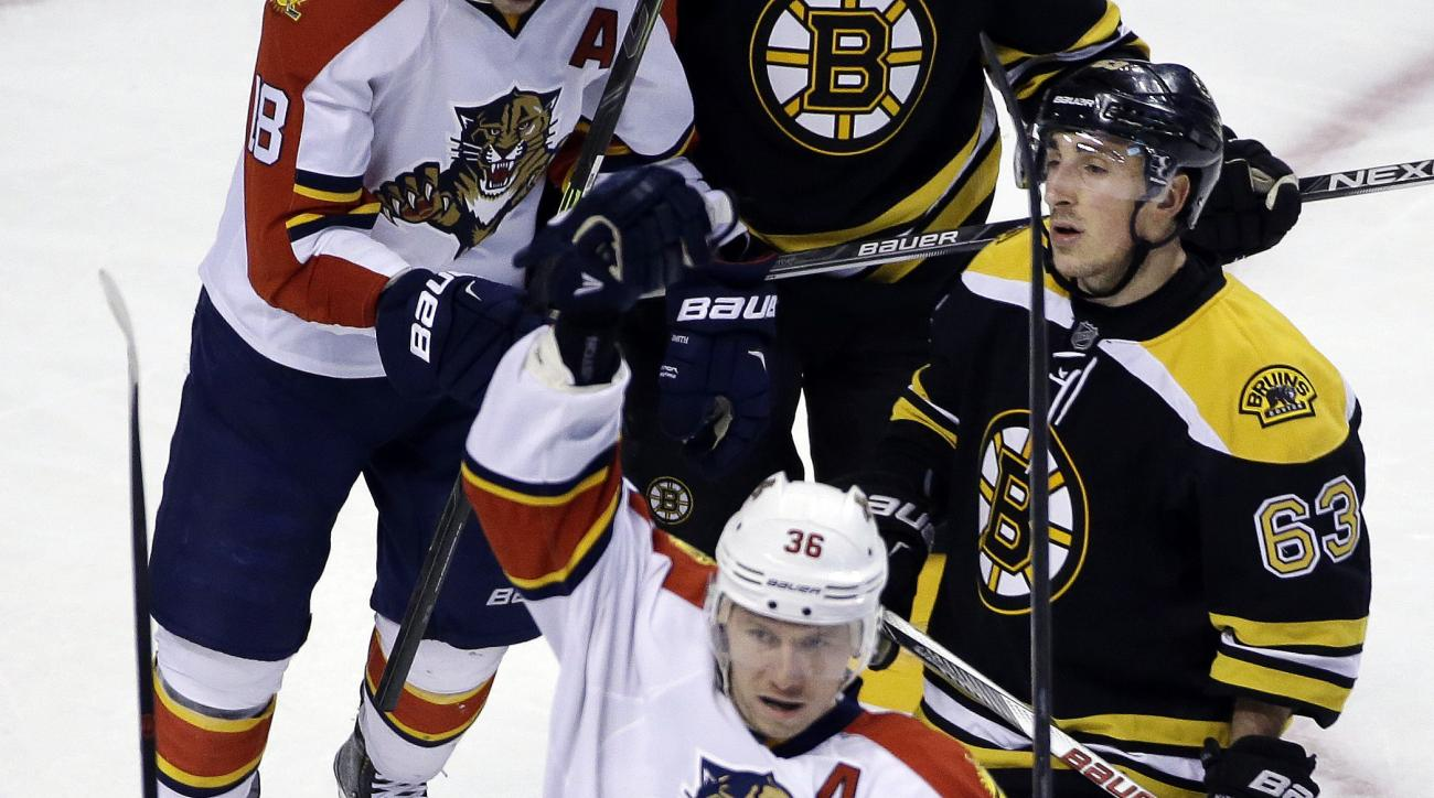 Florida Panthers left wing Jussi Jokinen (36) celebrates his goal with teammate Steven Kampfer (3) as Boston Bruins left wing Brad Marchand (63) looks on in the third period of an NHL hockey game, Thursday, March 24, 2016, in Boston. The Panthers won 4-1.