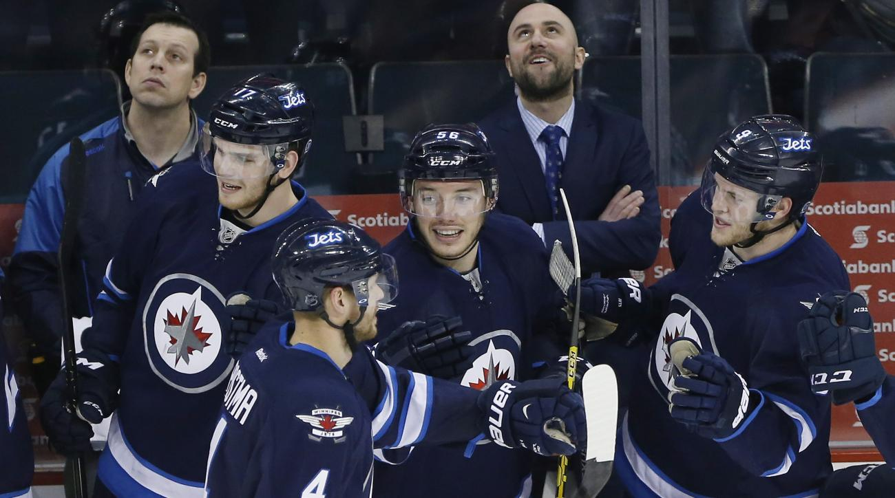 Winnipeg Jets' Adam Lowry (17), Paul Postma (4), Marko Dano (56) and Andrew Copp (9) celebrate Postma's goal against the Los Angeles Kings during the third period of an NHL hockey game Thursday, March 24, 2016,  in Winnipeg, Manitoba. (John Woods/The Cana