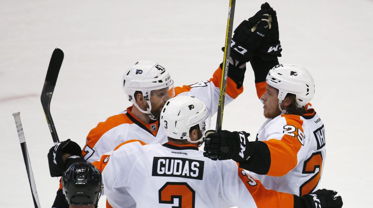Philadelphia Flyers center Ryan White, right, celebrates scoring an empty-net goal with defenseman Andrew MacDonald, left, and defenseman Radko Gudas, of the Czech Republic, against the Colorado Avalanche during the third period of an NHL hockey game Thur