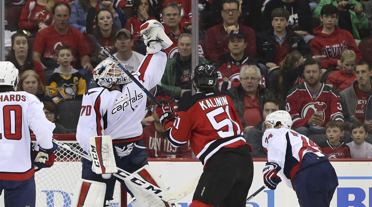 Washington Capitals goalie Braden Holtby (70) leaps to make a save in front of New Jersey Devils left wing Sergey Kalinin (51), of Russia, during the first period of an NHL hockey game Friday, March 25, 2016, in Newark, N.J. (AP Photo/Mel Evans)