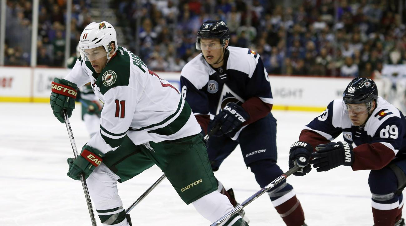 Minnesota Wild left wing Zach Parise, front, drives for a shot past Colorado Avalanche defenseman Erik Johnson, back left, and left wing Mikkel Boedker, of Denmark, in the second period of an NHL hockey game Saturday, March 26, 2016, in Denver. (AP Photo/