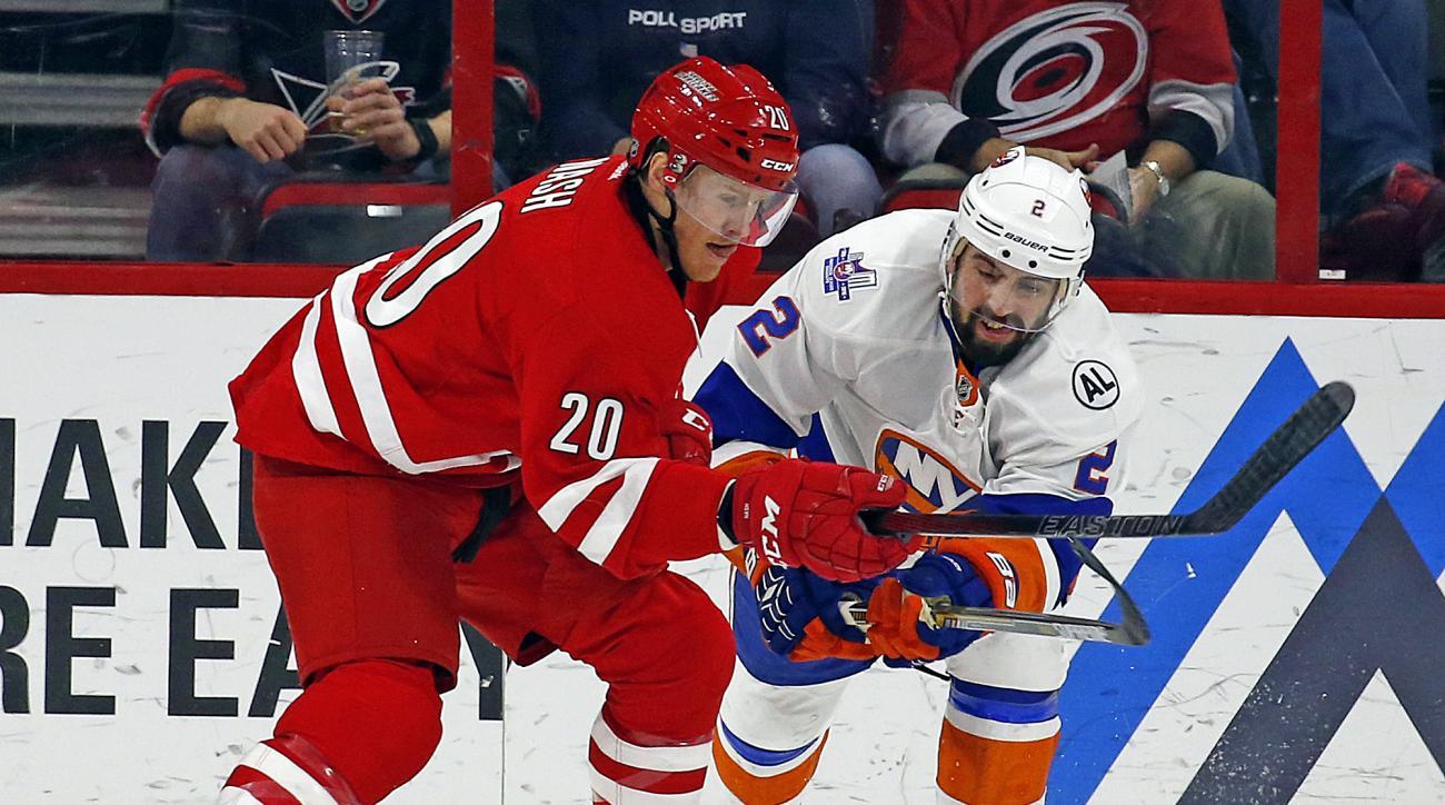 Carolina Hurricanes' Riley Nash (20) battles with New York Islanders' Nick Leddy (2) during the first period of an NHL hockey game, Saturday, March 26, 2016, in Raleigh, N.C. (AP Photo/Karl B DeBlaker)
