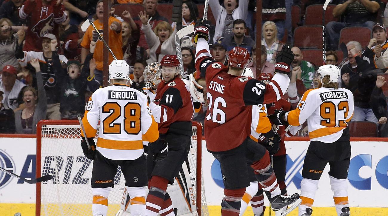 Arizona Coyotes' Michael Stone (26) celebrates his goal as teammate Martin Hanzal (11), of the Czech Republic, smiles at Stone while Philadelphia Flyers' Claude Giroux (28) and Jakub Voracek (93), of the Czech Republic, look for the puck during the second