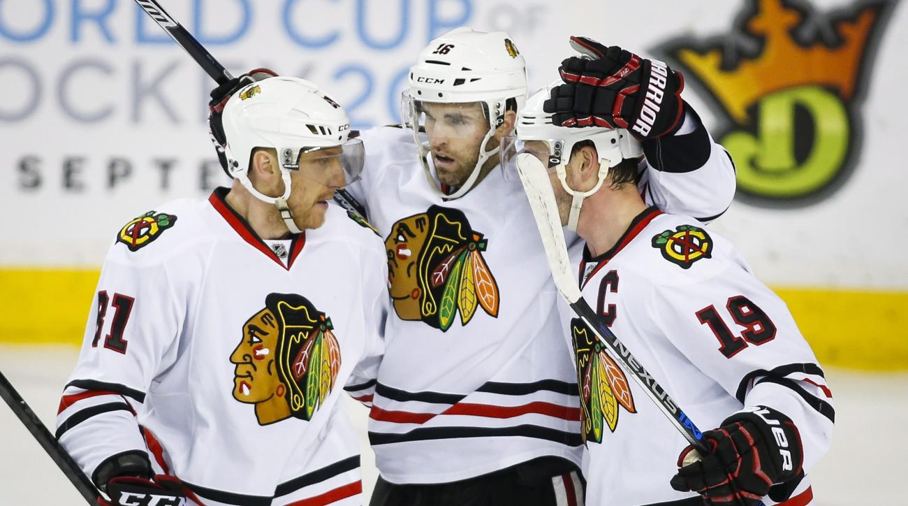 Chicago Blackhawks' Andrew Ladd, centre, celebrates his goal with teammates Marian Hossa, left, of Slovakia, and Jonathan Toews during third period NHL hockey action aainst the Calgary Flames in Calgary, Saturday, March 26, 2016.(Jeff McIntosh/The Canadia