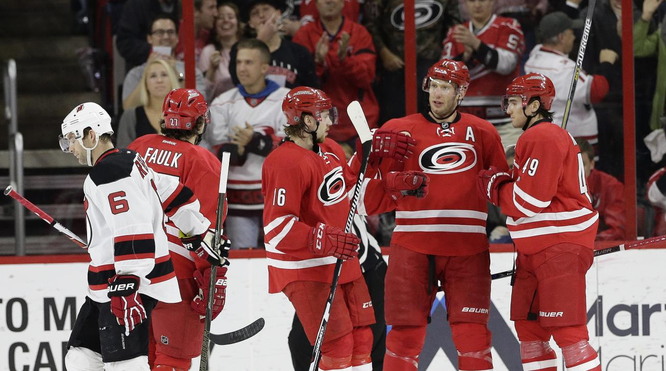 New Jersey Devils' Andy Greene (6) skates away as Carolina Hurricanes' Elias Lindholm (16), of Sweden, Jordan Staal and Victor Rask (49) celebrate Rask's goal during the first period of an NHL hockey game in Raleigh, N.C., Sunday, March 27, 2016. Carolina