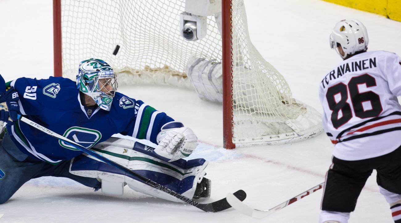 Chicago Blackhawks' Teuvo Teravainen, right, of Finland, scores against Vancouver Canucks' goalie Ryan Miller during the third period of an NHL hockey game in Vancouver, British Columbia, Sunday, March 27, 2016. (Darryl Dyck/The Canadian Press via AP)