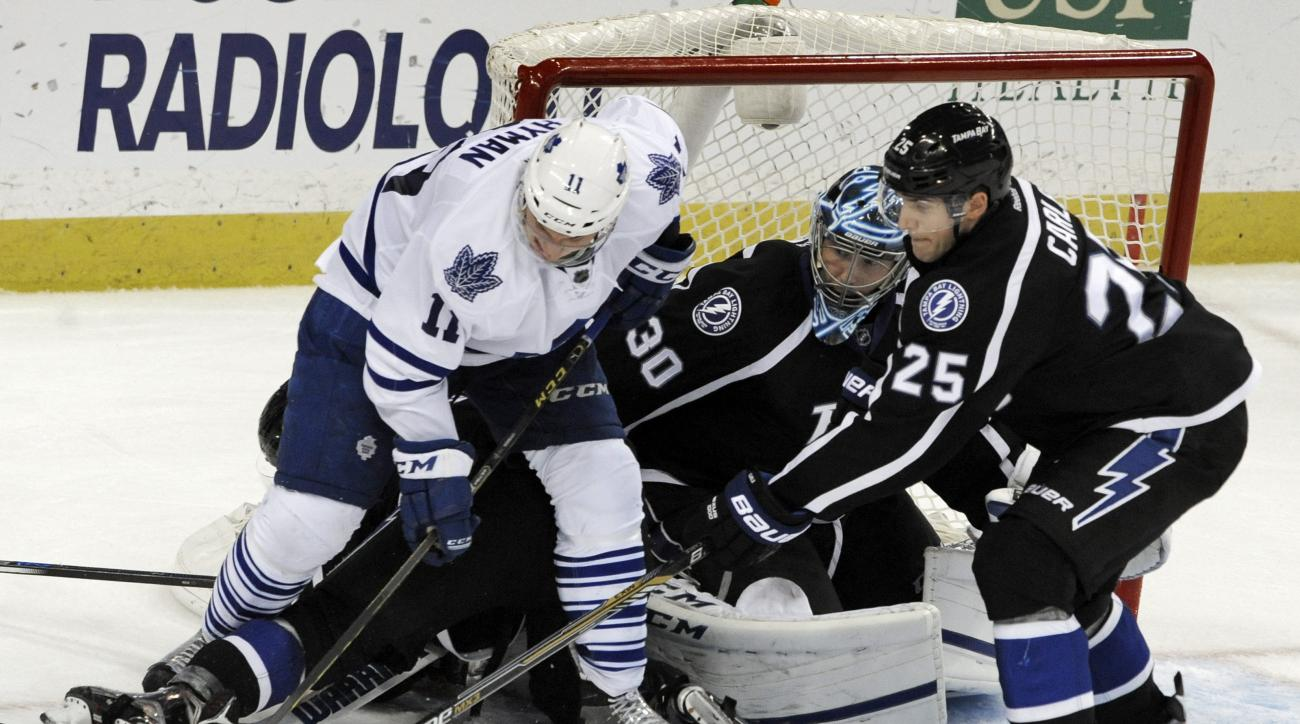 Tampa Bay Lightning's Matthew Carle (25) helps goalie Ben Bishop (30) defend the net from Toronto Maple Leafs' Zach Hyman (11) during the second period of an NHL hockey game, Monday, March 28, 2016, in Tampa, Fla. (AP Photo/Steve Nesius)