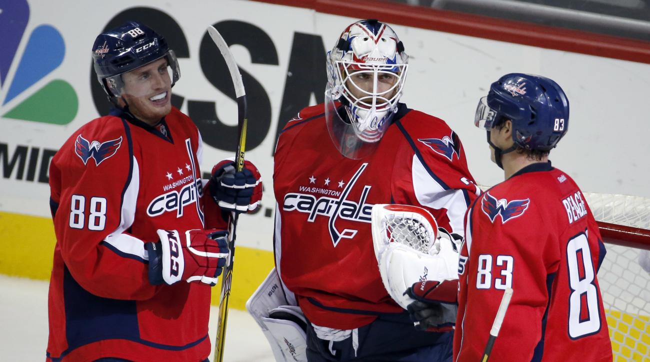 Washington Capitals goalie Braden Holtby, center, celebrates with defenseman Nate Schmidt (88) and center Jay Beagle (83) after an NHL hockey game against the Columbus Blue Jackets, Monday, March 28, 2016, in Washington. The Capitals won 4-1. (AP Photo/Al