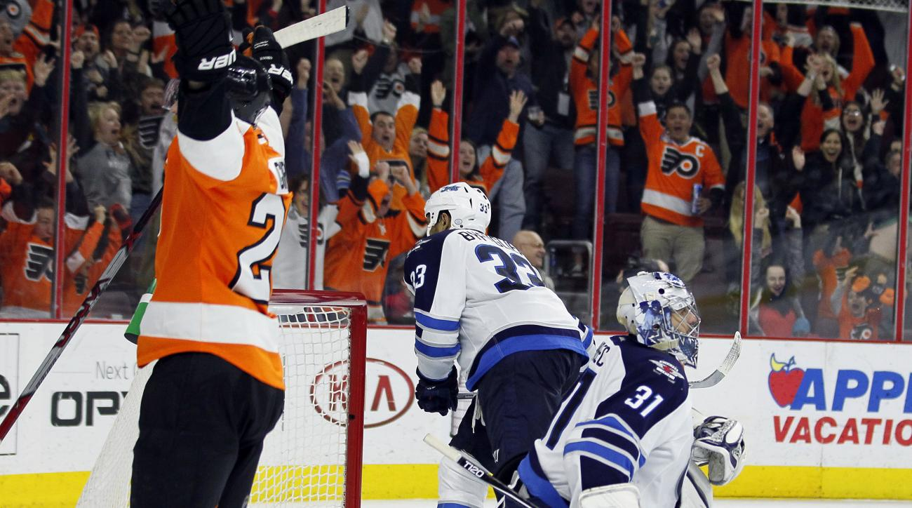 With the game-winning goal in the net Philadelphia Flyers' Claude Giroux, left, raises his arms after scoring past Winnipeg Jets' Ondrej Pavelec, right, during the overtime period of an NHL hockey game Monday, March 28, 2016 in Philadelphia. The Flyers wo