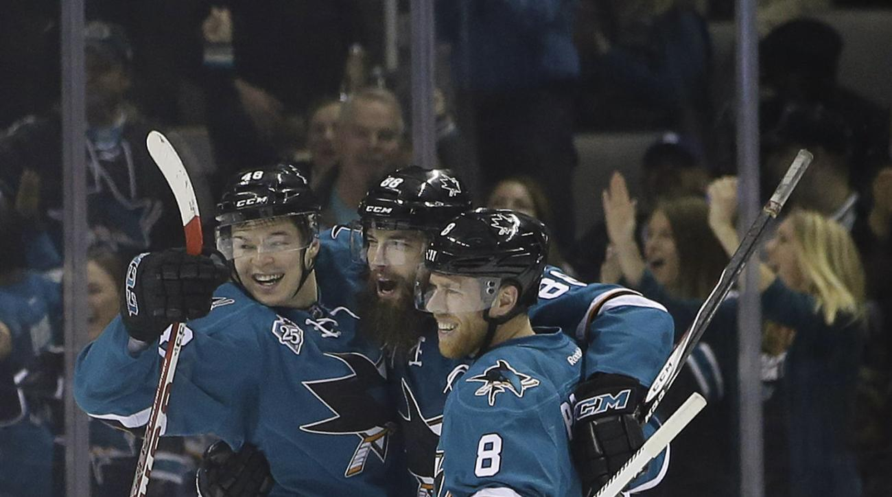 San Jose Sharks' Brent Burns, center, celebrates his goal with teammates Tomas Hertl, left, and Joe Pavelski (8) during the second period of an NHL hockey game against the Los Angeles Kings Monday, March 28, 2016, in San Jose, Calif. (AP Photo/Marcio Jose