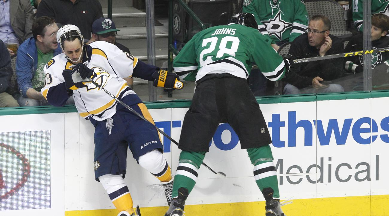 Nashville Predators center Mike Ribeiro (63) is shoved against the boards by Dallas Stars defenseman Stephen Johns (28) during the first period of an NHL hockey game Tuesday, March 29, 2016, in Dallas.  (AP Photo/Tim Sharp)