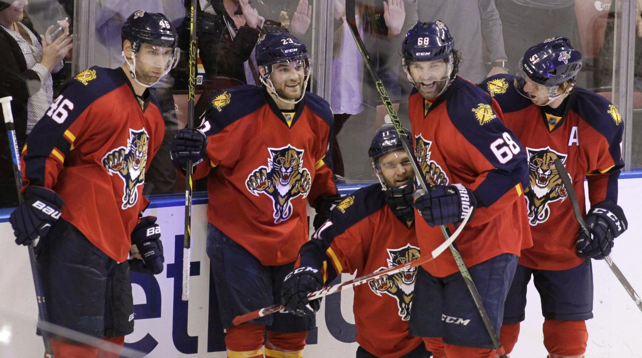 Florida Panthers Jonathan Huberdeau, third from left, celebrates with teammates Jakub Kindl (46), of the Czech Republic,  Rocco Grimaldi, second from left, Jaromir Jagr (68), of the Czech Republic, and Brian Campbell, right, after scoring a goal during th