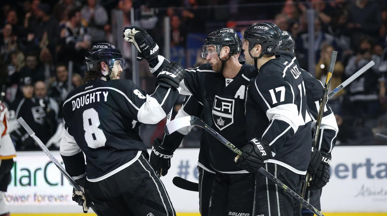 Los Angeles Kings center Jeff Carter, second from left, celebrates his power-play goal with teammates, including Drew Doughty, left, and Milan Lucic, right, against the Calgary Flames during the second period of an NHL hockey game, Thursday, March 31, 201