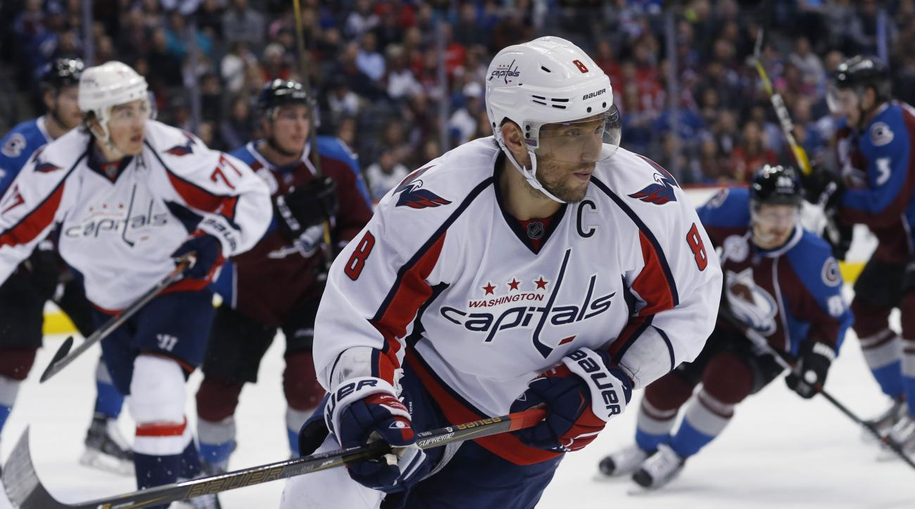 Washington Capitals left wing Alex Ovechkin, front, of Russia, pursues the puck while facing the Colorado Avalanche in the second period of an NHL hockey game Friday, April 1, 2016, in Denver. (AP Photo/David Zalubowski)