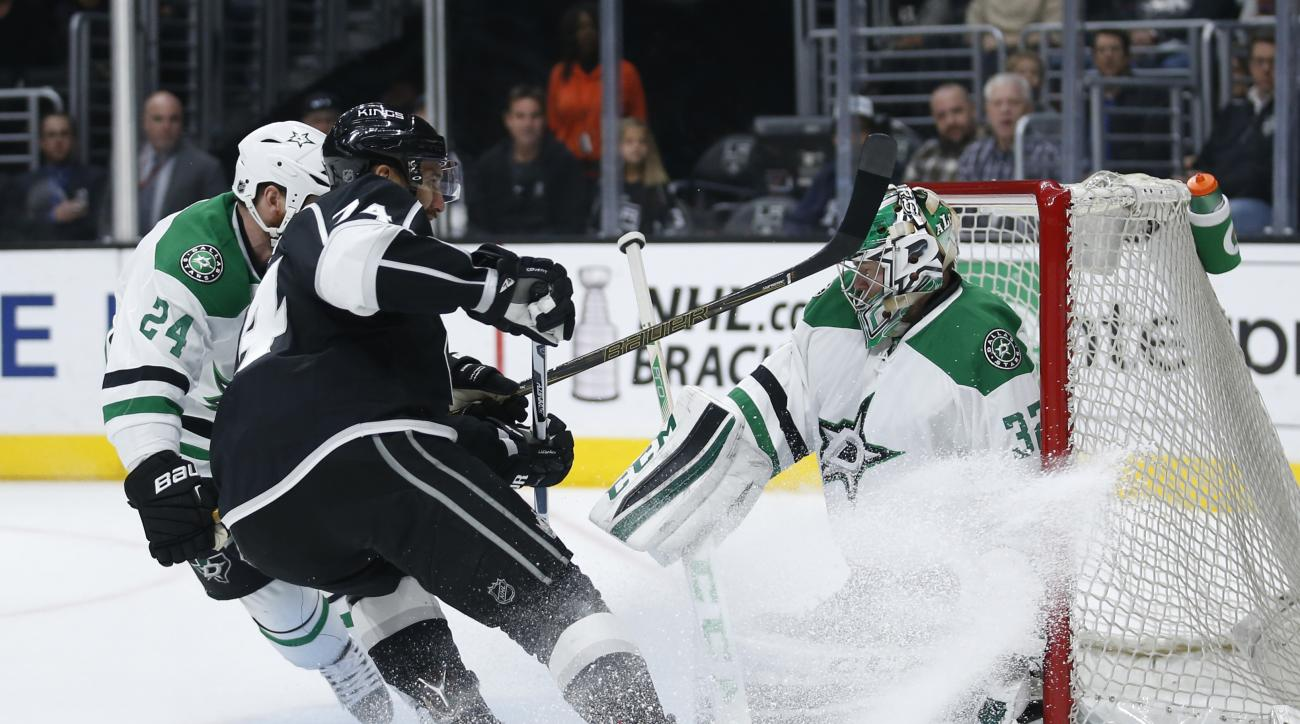 Los Angeles Kings left wing Dwight King, center, looks for a rebound while Dallas Stars goalie Kari Lehtonen protects the net and Stars' Jordie Benn, left, also defends during the second period of an NHL hockey game, Saturday, April 2, 2016, in Los Angele