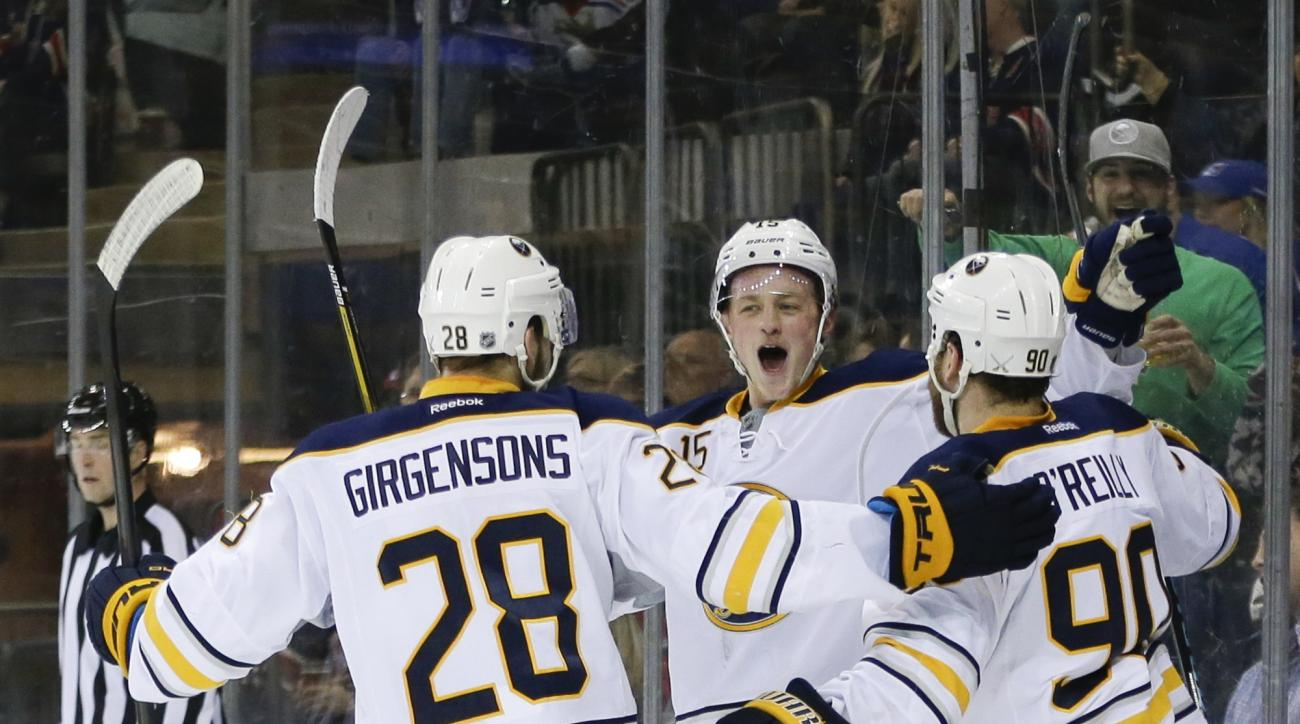 Buffalo Sabres' Jack Eichel, center, celebrates with teammates Zemgus Girgensons (28) and Ryan O'Reilly (90) after O'Reilly's second goal in the first period of an NHL hockey game against the New York Rangers on Saturday, April 2, 2016, in New York. (AP P