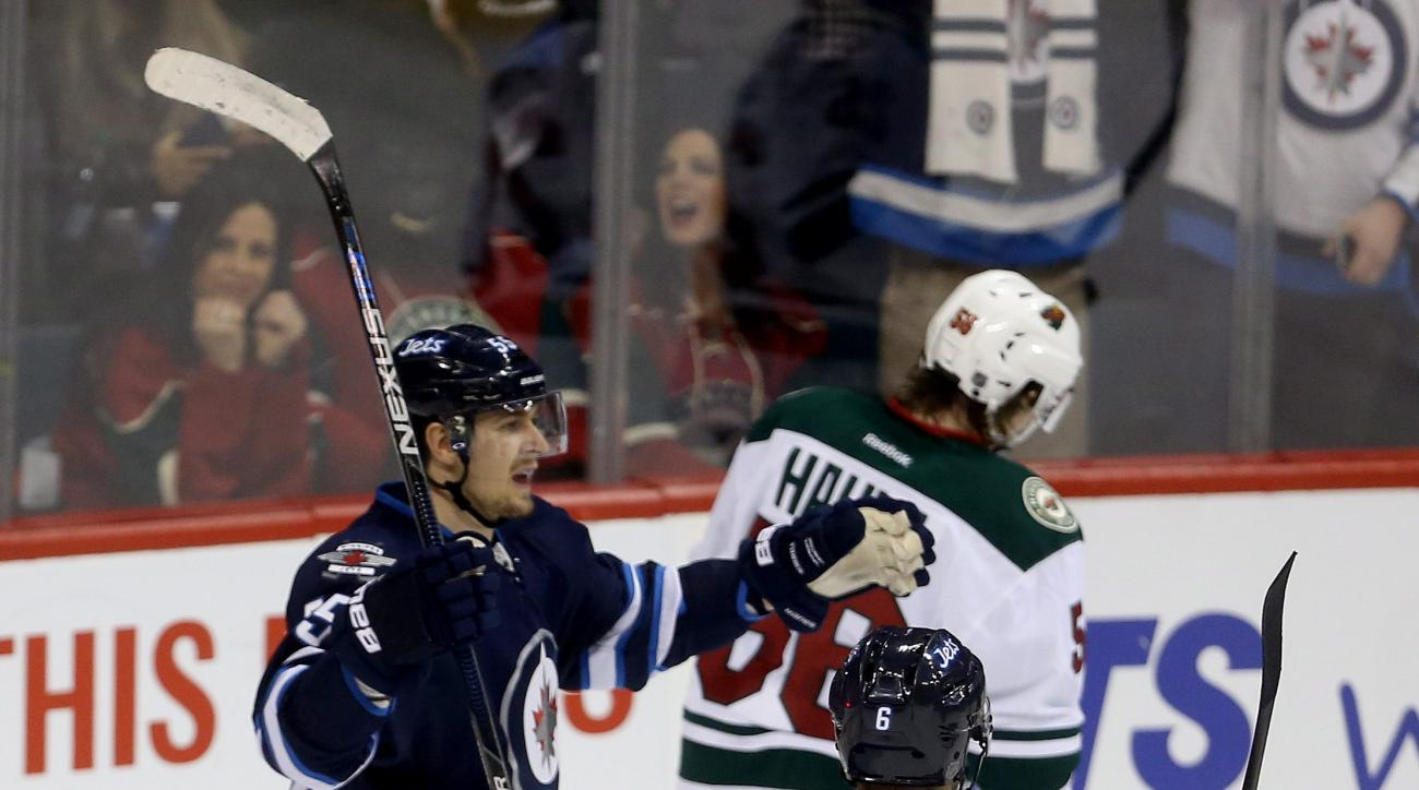 Winnipeg Jets' Mark Scheifele (55) celebrates with Alexander Burmistrov (6) after scoring on the Minnesota Wild during first period NHL hockey action in Winnipeg, Canada, Sunday, April 3, 2016. (Trevor Hagan/The Canadian Press via AP)