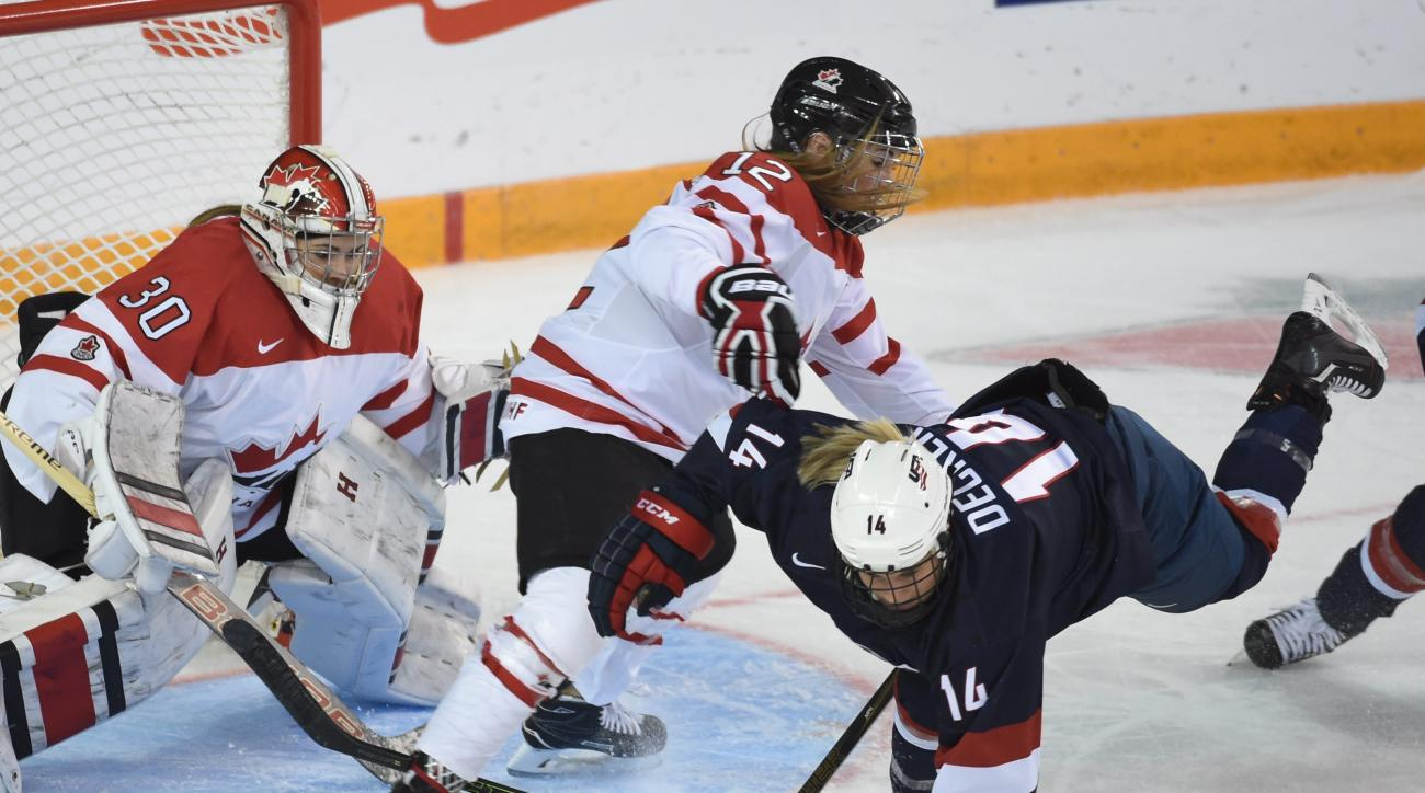 United States's Brianna Decker (14) goes flying in front of Canada's Meaghan Mikkelson (12) and goalie Emerance Maschmeyer in first period of the women's world hockey championships Monday, April 4, 2016, in Kamloops, British Columbia. (Ryan Remiorz/The Ca